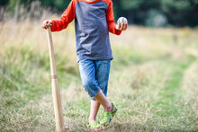 A Happy Child With Baseball Bat On Nature Concept In Park