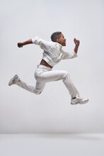 Energetic Black Model Jumping While Running On Light Background