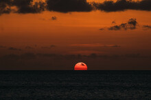 Glorious Scenery Of The Sun Setting Down On The Horizon By The Ocean With Orange Ombre Sky