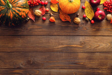 Harvest Or Thanksgiving Background With Ripe Orange Pumpkins, Fallen Leaves, Dry Flowers On Rustic Wooden Table. Flat Lay, Top View, Copy Space.