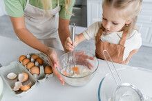 Child Mixing Chicken Eggs And Flour With Whisk Near Mother Holding Bowl