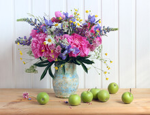 Summer Bouquet Of Peonies Irises Daisies Buttercups On The Table In A Jug