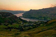 Looking Down Towards Glenridding And Ullswater From The Path Up Helvellyn In The Lake District. Shot In Landscape At Sunset, Showing Beautiful Soft Peach And Yellow Sky