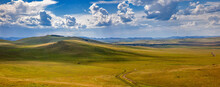 Panoramic Views Of The Hills And Steppe. Yellow Field Under Blue Sky With Dramatic Clouds, Khakasia, Russia.