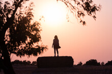 Silhouette Of A Woman In The Field On A Straw Bale At Sunset With The Sun Behind Her And Tree Branches On Her Sides