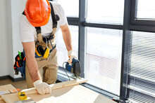 Man Working As Handyman, Assembling Wood Table With Equipments, Concept For Home Diy And Self Service. Male In Orange Hardhat And Overalls Concentrated Focused On Work, Using Electric Tools