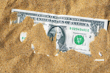 Top View Of One Dollar Banknote Buried In The Sand. Closeup Of Dollar Bill In The Sand.