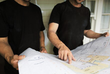 Team Members Pointing At Architectural Drawing And Problem Solving At Construction Site