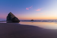 Beautiful Landscape. Ocean. There Are Two Rocks On The Sandy Shore. Evening. Sunset. There Are Light White Clouds In The Blue Sky. Majestic Nature. Calm Scenes. There Is No One In The Photo.