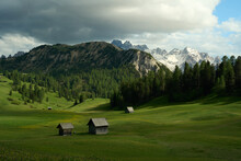 Scenic View Of Wooden Huts In A Green Field On A Mountainous Background