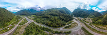 A Large Aerial Panorama Of The Valley Of The Mountain River Mzymta, Surrounded By Highways And Forested Green Mountains Of The Caucasus. Cable-stayed Bridge Over The River Entering The Tunnel
