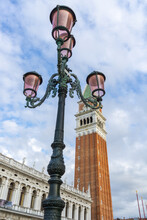Venetian Lamppost With The Bell Tower Of San Marcos In The Background, With A Sky Full Of White Clouds