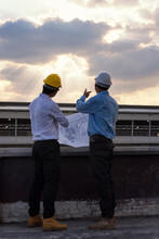 Rear View Of Engineers Analyzing Blueprint While Standing On Building Terrace At Sunset