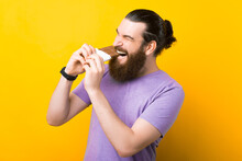 Excited Young Bearded Man Is Biting A Bar Of Chocolate Over Yellow Background.