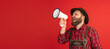 canvas print picture - Comic portrait of bearded man, waiter in hat and traditional Bavarian costume shouting at megaphone isolated over red studio background. Oktoberfest, fest, holidays concept