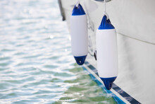Two White Fenders Suspended Between A Boat And Dockside For Protection. Maritime Fenders