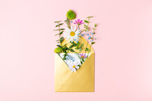 Golden Envelope With Beautiful Spring Garden Flowers On Pink Background