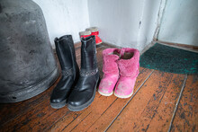 Kids Old Winter Boots Laying On The Wooden Floor