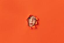 Little Boy Peeking Through Orange Torn Paper