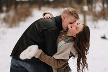 A Man And A Woman In Love In Outerwear Are Having Fun Hugging Walking Outside The City Among The Trees In The Winter Forest During The Christmas Holidays, A Selective Focus