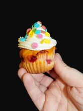 In The Hand, A Yogurt Muffin With Red Currants, Smeared With White Cream From Cream And Mascarpone, Decorated With Colorful Round Splashes On A Black Background, Side View . Homemade Cakes