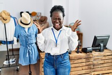 Young African Woman Working As Manager At Retail Boutique Celebrating Mad And Crazy For Success With Arms Raised And Closed Eyes Screaming Excited. Winner Concept