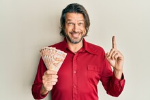Middle Age Handsome Man Holding 50 Turkish Lira Banknotes Smiling With An Idea Or Question Pointing Finger With Happy Face, Number One