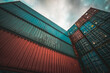 Cargo container for overseas shipping on high stack look up from ground . Logistics supply chain management and international goods export concept .