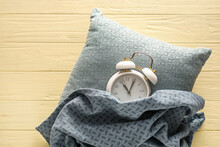 Alarm Clock With Pillow And Blanket On Color Wooden Background
