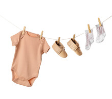 Baby Clothes And Shoes Hanging On Rope Against White Background