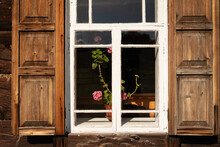 Flowers In Pot On The Window Sill Of Wooden House