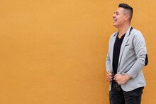 Man Against Yellow Wall. Latin Man Laughing Very Loud And Looking Far Away. Concept Of Expressions With Copy Space On Single Color Background.