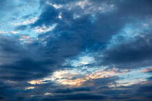 Blue Clouds With Twilight . Sun Glowing In The Dark Clouds