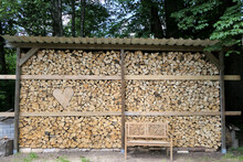 A Firewood Wall With A Wooden Heart And A Bench To Dream About.