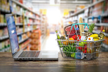Grocery Food Buying Online And Delivery Concept. Shopping Basket Full Of Food  And Laptop On The Shelf Of Supermarket.