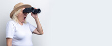 Surprised Old Woman Holding Binoculars On A Light Background. Banner