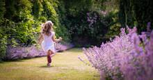 Girl Running Through A Summer Garden With Cat Mint