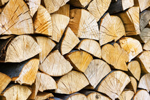 Stacked Chopped Wood Close-up Texture. Firewood Storage Background. Stocks Of Wooden Logs. Chopping Wood For A Fireplace. Woodpile With Firewood With Visible Wooden Texture.