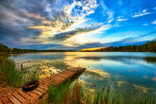 Wooden Dock In Calm Water At Sunset