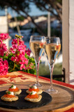 Russian style party with two glasses of white cold champagne, bliny with red caviar and view on Port Grimaud near Saint-Tropez in summer