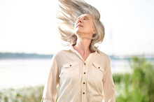 Gray-haired Energetic Woman With Hair Fluttering In Wind