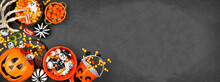 Halloween Trick Or Treat Corner Border With Jack O Lantern Pails And A Variety Of Candy. Above View On A Black Banner Background With Copy Space.