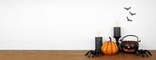 Halloween Shelf Display With Candles And Decor Against A White Wall With Bats. Wood Shelf. Banner With Copy Space.