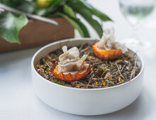 Detail Of A Haute Cuisine Dish Made With Two Small Mushroom Tarts On A Base Of Dried Herbs.