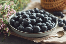 Blue Plate Of Fresh Blueberries And Heather Flowers On Kitchen Table.