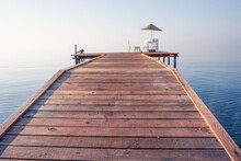 Wooden Pier With Rope Railings Extending Into The Sea On A Misty Summer Morning. There Are Beach Umbrella, Chairs And Tables On The Pier. A Mystical Seascape With An Endless Natural Backdrop.