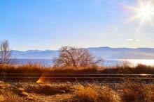 Circum Baikal Railway Running Along The Shore Of Lake Baikal On An Autumn Sunny Day With A Yellow Landscape Around