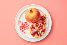 Juicy Pomegranate With Seeds On White Plate On Pink Pastel Table Top-down. Copy Space