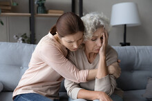 Worried Stressed Young Woman Cuddling Depressed Emotional Unhappy Middle Aged Old Retired Mother, Asking Forgiveness Or Supporting In Difficult Life Situation, Comforting Or Soothing At Home.
