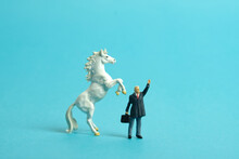 Miniature People Toy Figure Photography. A Businessman Standing In Front Of Prancing Horse While Raise His Hand. Isolated On Blue Background